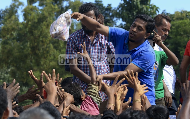 Rohingya refugees stretch their hands for relief materials at Palongkhali in Ukhia, Cox's Bazar as aid workers throw clothes from a truck. bdnews24.com
