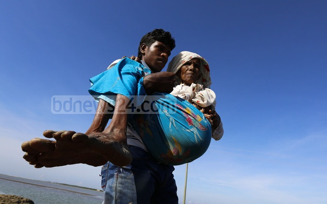 Maungdaw resident Mir Kashem carries his sick mother Gulbahar after the crossing the Bangladesh-Myanmar border in Cox's Bazar's Teknaf. Photo: mostafigur rahman