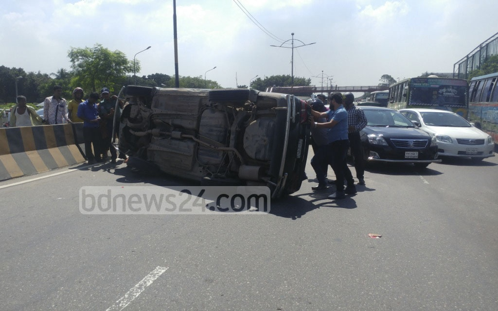 Locals rescue the driver of a car after it overturns in an accident on Dhaka's Kuril Biswa Road. Photo: abdul mannan
