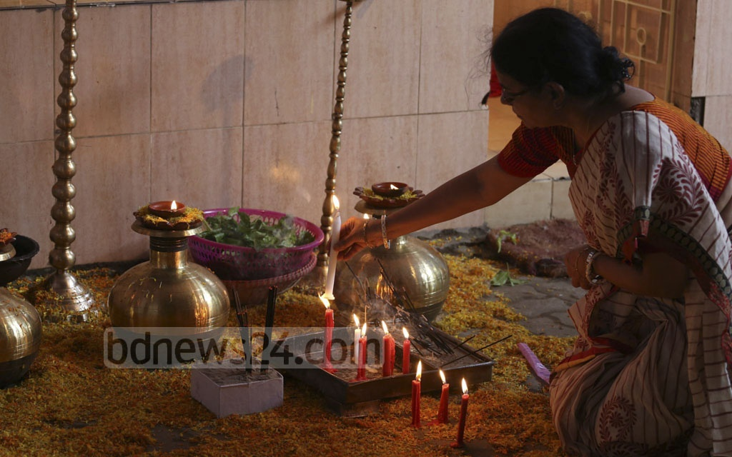 A devotee lights up candles at Dhakeshwari National Temple on Tuesday to celebrate Mahalaya that ushers in a countdown to Durga Puja.