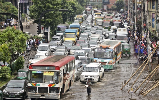 Traffic builds up on a busy Dhanmondi street overrun by rainwater on Wednesday.