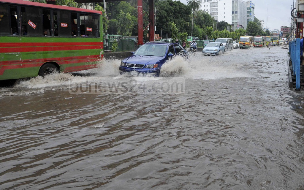 A car sprays water as it crosses the west side of the Mirpur road flooded by rainwater on Wednesday.