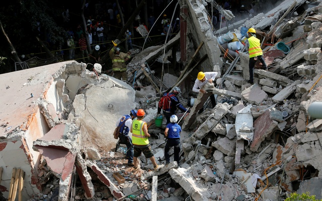 Rescue personnel remove rubble at a collapsed building while searching for people after an earthquake hit Mexico City, Mexico Sept 19, 2017. Reuters