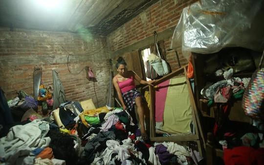 Ximena, 26, an indigenous Zapotec transgender woman also know as Muxe, walks on her belongings inside her house destroyed after an earthquake that struck on the southern coast of Mexico late on Thursday, in Juchitan, Mexico, September 10, 2017. Picture taken, September 10, 2017. REUTERS