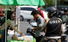An Uber motorcycle taxi driver stops at a food stall next to a shopping mall in Jakarta, Indonesia Sept 20, 2017. Reuters