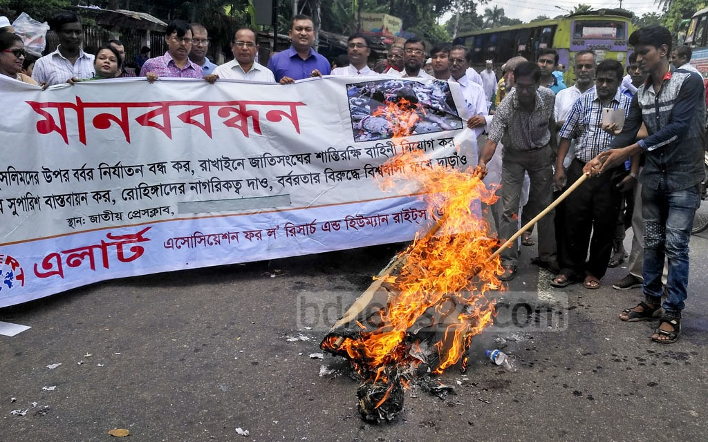 Demonstrators burn an effigy of Myanmar leader Aung San Suu Kyi in fornt of the National Press Club in Dhaka on Saturday to protest against the persecution of Rohingyas in Rakhine State .