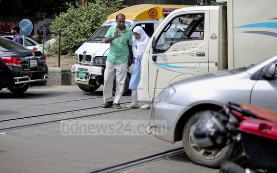 Typical jaywalkers in the capital: Pedestrians risk their lives to cross the street at Mohakhali level crossing in Dhaka as speedy vehicles pass by. This photo is taken Saturday afternoon. Photo: asaduzzaman pramanik