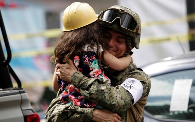 A girl hugs a Mexican marine officer as she offers hugs to people near the site of a collapsed building after an earthquake, in Mexico City, Mexico Sept 23, 2017. Reuters