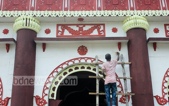 A painter gives final touches to a well-decorated Puja Mandap built on Bananai playground on Monday, a day before the begining of the biggest Hindu festival, Durgan Puja.