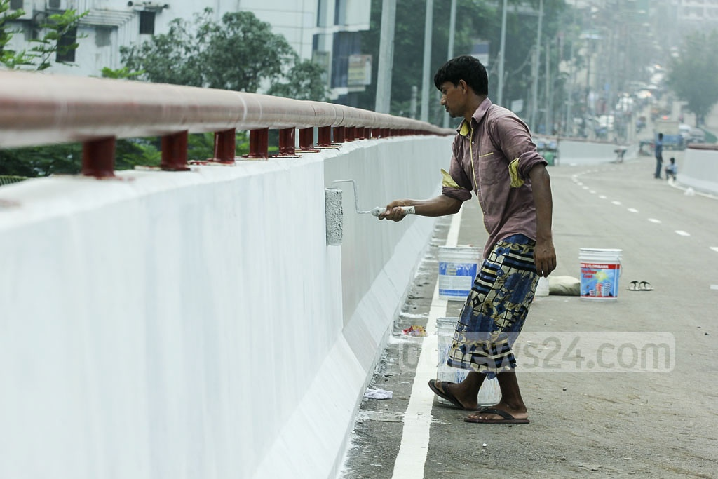 A worker paints the walls of the Moghbazar-Mouchak flyover as preparation for its imminent inauguration.