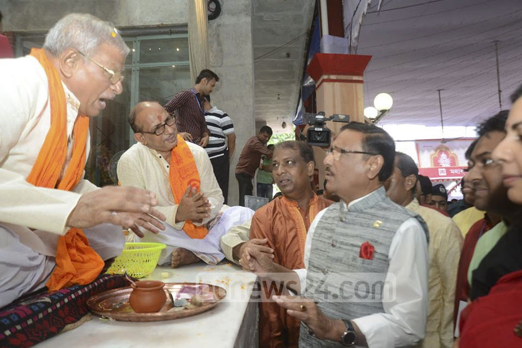 Obaidul Quader, general secretary of the ruling Awami League, interacts with priests performing Nabami rituals for Durga puja at Dhaka's Dhakeshwari Temple on Friday.