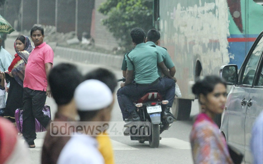 Law enforcers, who are tasked with supervising safe commute, take the unsafe ways, setting a poor example for citizens. In this photo taken at Mohakhali in Dhaka on Friday, a policeman is seen riding a motorcycle with two of his colleagues on the pillion seats, all without helmet. Photo: abdul mannan