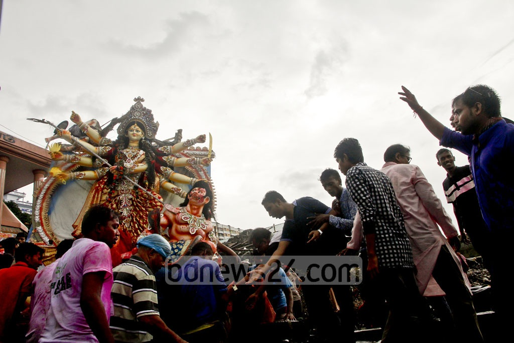 Hindu devotees carry an idol of goddess Durga for immersion in the river Burhiganga at Dhaka's Wise Ghat on Saturday by the end of their largest festival Durga Puja. Photo: tanvir ahammed