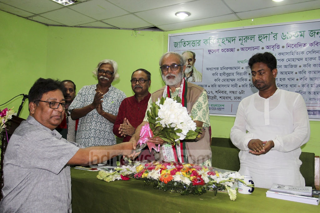 Friends, fans and well wishers shower poet Muhammad Nurul Huda with wreaths and respects at a reception organised on his birthday at the National Public Library auditorium in Dhaka on Saturday.