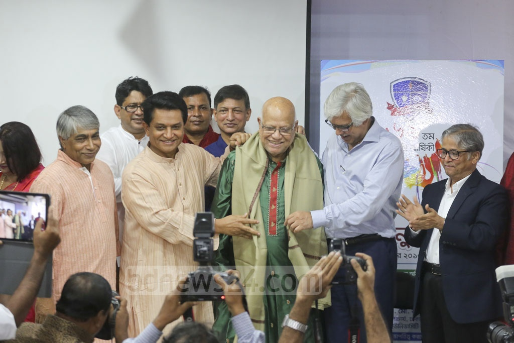 Dhaka University Alumni Association President AK Azad dons a sash on Finance Minister AMA Muhith, who is also a member of the association, at a programme marking its 68th anniversary on Sunday.