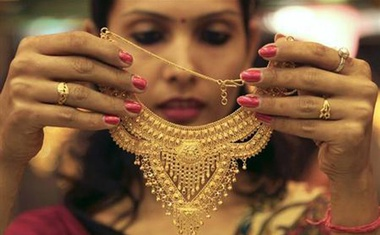 A salesgirl shows a gold necklace to customers at a jewellery showroom in Chandigarh Nov 11, 2012. Reuters