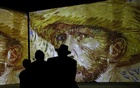 People look at the works of Vincent Van Gogh, projected on the wall during the opening exhibition
