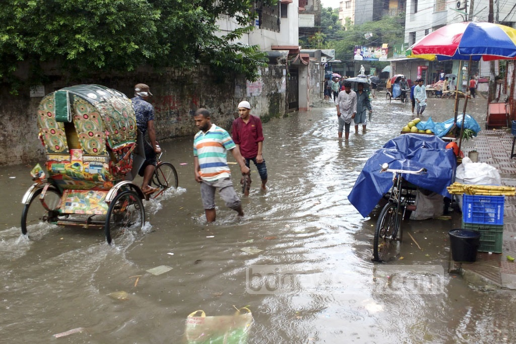 Inundated streets in the capital's Mohammadpur on Friday left pedestrians suffering after an hour of rain. Photo: md asaduzzaman pramanik