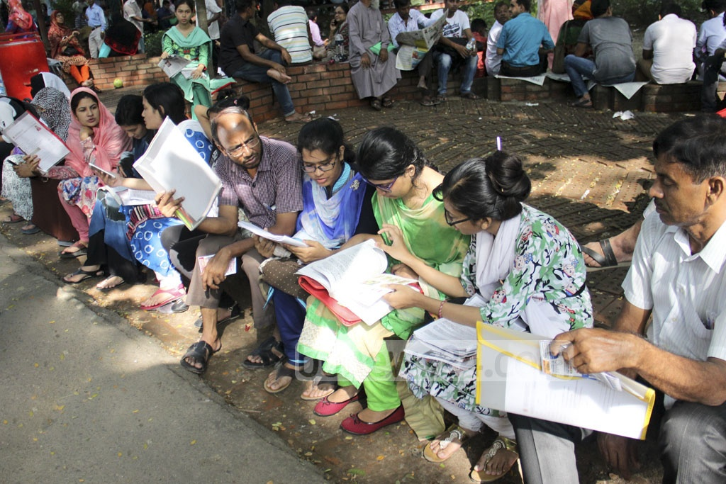 Medical college admission test candidates take last-minute preparations before the exam outside Dhaka University's Arts Building on Friday.