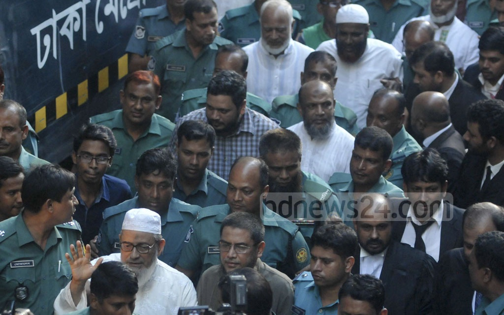 Police escort eight Jamaat-e-Islami leaders, including its chief Maqbul Ahmed, Secretary General Shafiur Rahman and policymaking body member former MP Mia Golam Parwar, to a court on Tuesday after showing them arrested in two cases.