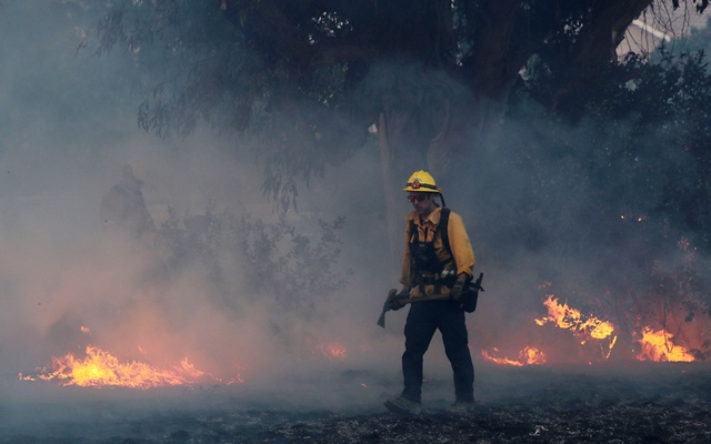 A firefighter works to put out hot spots on a fast moving wind driven wildfire in Orange, California, US, Oct 9, 2017. Reuters