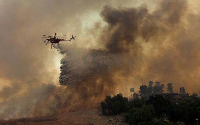 A firefighting helicopter drops water to help save a home during a wind driven wildfire in Orange, California, US, Oct 9, 2017. Reuters
