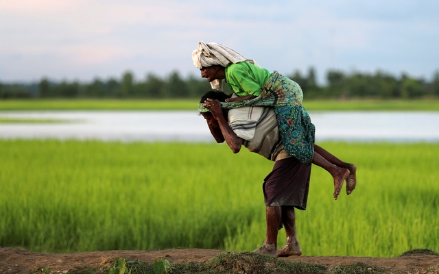 A Rohingya refugee man carries an elderly woman after crossing the border in Palang Khali, Bangladesh, Oct 9, 2017. Reuters