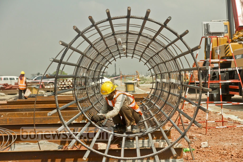 Workers busy at the Metrorail project construction site at Diyabari in Dhaka's Uttara. The elevated train service will have 16 stations and it will take approximately 38 minutes to reach Motijheel from Uttara. Photo: tanvir ahammed