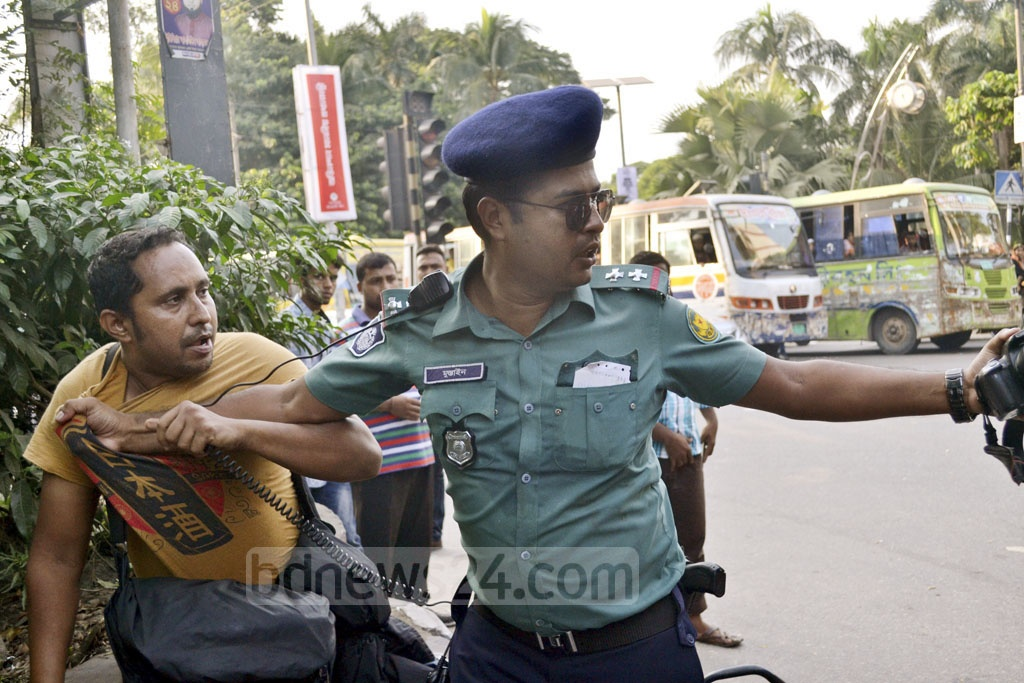 A Dhaka traffic police officer manhandles a motorbike rider on Wednesday after penalising him for not wearing a helmet. The rider, Nasiruddin Ahmed, who works as a photojournalist for a newspaper, claims he was assaulted by the officer and that his camera was snatched away.