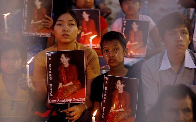 People hold Myanmar state counselor Aung San Suu Kyi photos during the ceremony of interfaith praying in Yangon, Myanmar October 10, 2017. Reuters