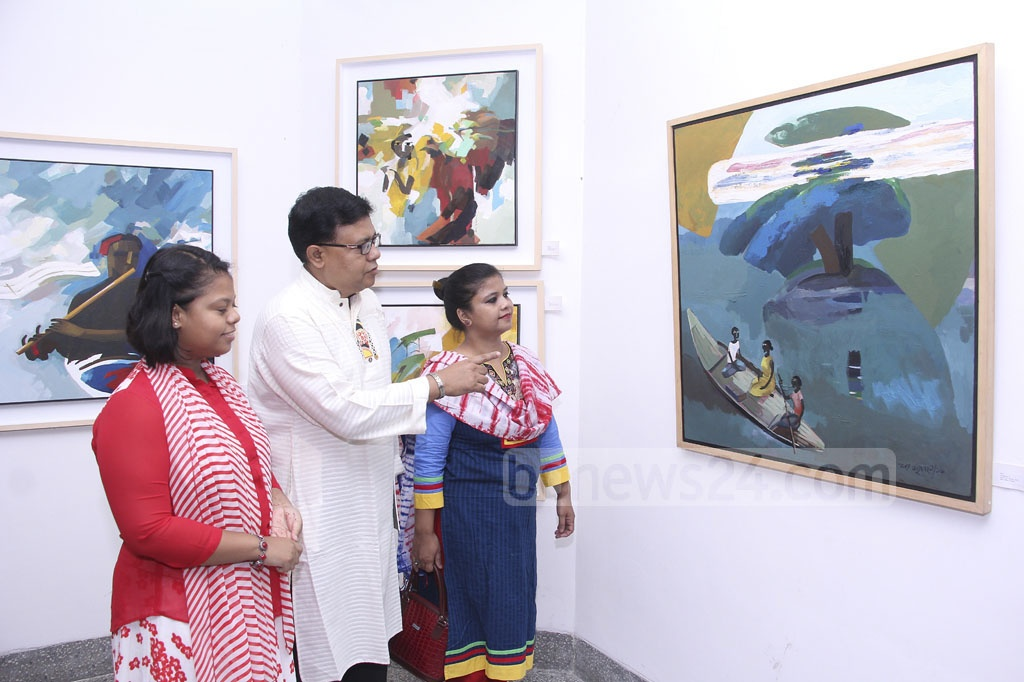 Visitors appreciate a work of artist Samar Majumder at his solo painting exhibition 'Mrittika Maya' or Earthen Affection at La Galerie, Alliance Française de Dhaka on Friday.