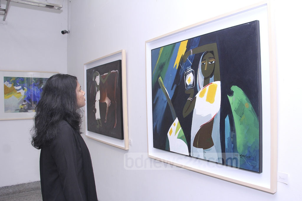 A visitor appreciates a work of artist Samar Majumder at his solo painting exhibition 'Mrittika Maya' or Earthen Affection at La Galerie, Alliance Française de Dhaka on Friday.