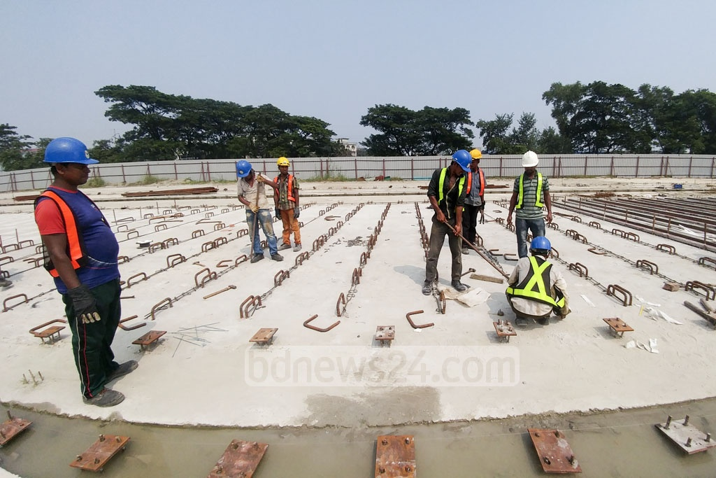 Construction workers for Dhaka's elevated expressway project work in a yard across from Dhaka's Hazrat Shahjalal International Airport. Photo: abdul mannan