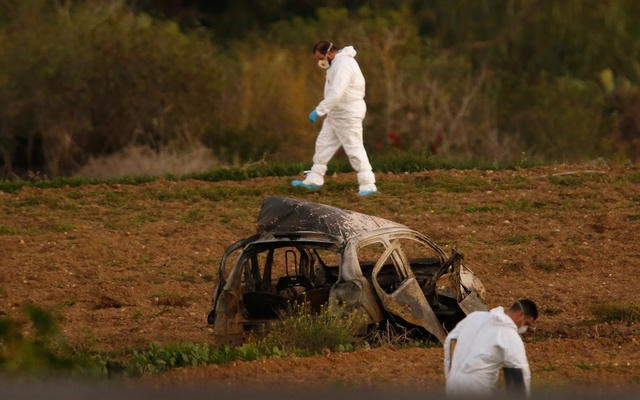Forensic experts walk in a field after a powerful bomb blew up a car (Foreground) and killed investigative journalist Daphne Caruana Galizia in Bidnija, Malta, Oct 16, 2017. Reuters