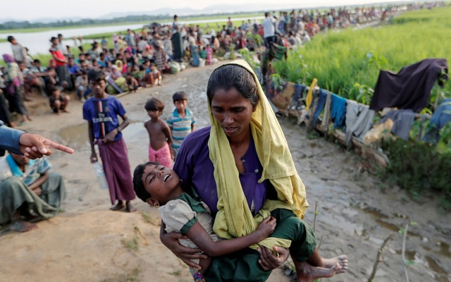 A Rohingya refugee woman who crossed the border from Myanmar a day before, carries her daughter and searches for help as they wait to receive permission from the Bangladeshi army to continue their way to the refugee camps, in Palang Khali, Bangladesh Oct 17, 2017. Reuters