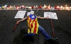 A man lays down on the ground with an Estelada (Catalan separatist flag) next to candles during a protest against the imprisonment of leaders of two of the largest Catalan separatist organizations, Catalan National Assembly's Jordi Sanchez and Omnium's Jordi Cuixart, who were jailed by Spain's High Court, in Barcelona, Spain Oct 17, 2017. Reuters