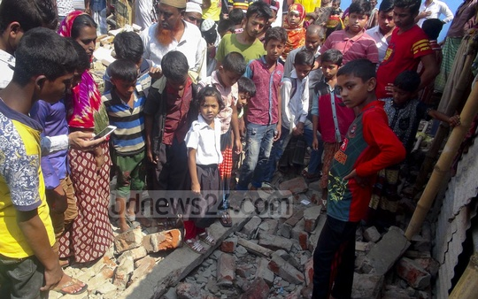 Locals crowd around a collapsed wall in Narayanganj's Sadar Upazila that caused the deaths of four, including three girls.