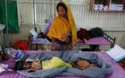 Ruaida Begum (L), 3, suffering from severe malnutrition, and her brother Nurul Amin, 1, suffering from pneumonia, lie on a bed as their mother stands next to them at a diarrhoea treatment centre in Kutupalong refugee camp near Cox's Bazar, Bangladesh Oct 28, 2017. Reuters