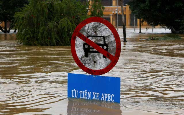 A traffic sing indicating APEC summit vehicles priority is seen along submerged street in UNESCO heritage ancient town of Hoi An after typhoon Damrey hits Vietnam November 6, 2017. Reuters