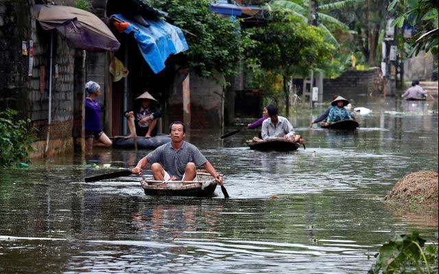Residents paddle boats, in a flooded village, after heavy rain, caused by a tropical depression in Hanoi, Vietnam October 17, 2017. Reuters