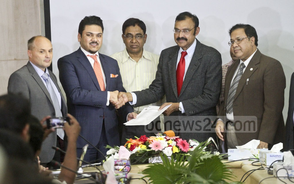 BTRC Chairman Shahjahan Mahmood hands the licence notice for MNP services, which allow mobile-phone users to change their operators without changing numbers, to Infozillion BD Teletech Managing Director Mabroor Hossain. Photo: dipu malakar