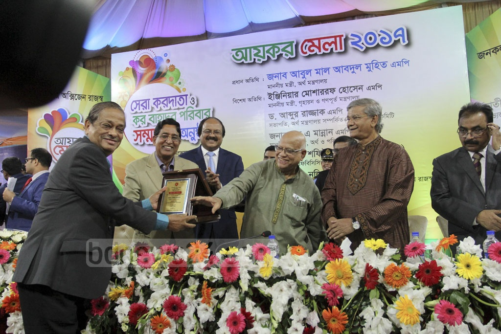 Bangla daily Samakal Editor Golam Sarwar receives the award from Finance Minister AMA Muhith as he was nominated as one of the best taxpayers for the 2016-17 financial year. Photo: asif mahmud ove