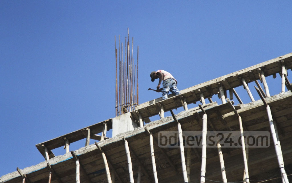 A construction worker works on a multi-storey building without wearing any safety gears, thereby putting his life in danger, at Mirpur in Dhaka on Tuesday. Photo: dipu malakar