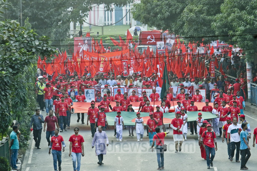 Workers Party activists carrying a national flag of Bangladesh along with red flags with hammer-sickle symbol and other slogans march in Dhaka on Saturday to mark the centenary of the Russian Revolution. Photo: tanvir ahammed