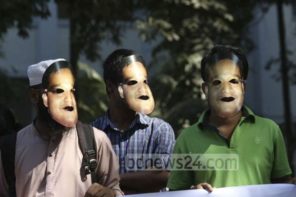 Teachers and students of Dhaka University's mass media and journalism department at a protest rally on Sunday in campus wearing masks resembling department alumnus Mubashar Hasan who has gone missing. Hasan was working as an assistant professor at North South University at the time of his disappearance. Photo: tanvir ahammed