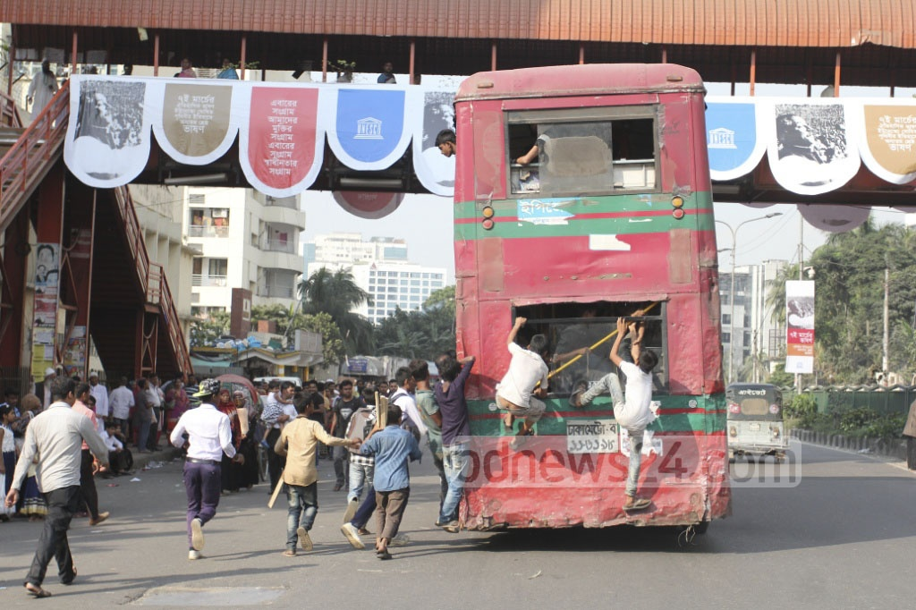 Some commuters risk their lives by clinging on to the back a double-decker bus that comes after a long wait. Most commuters services go off the streets in Dhaka on Sunday ahead of BNP rally at Suhrawardy Udyan. Photo: asif mahmud ove