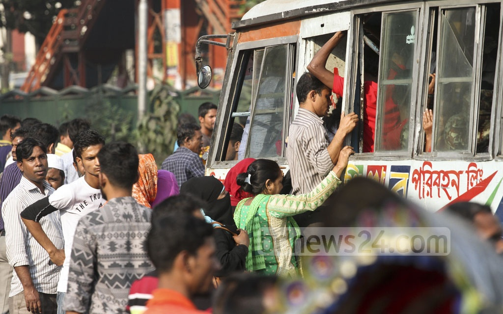 Some commuters risk their lives by clinging on to the back a double-decker bus that comes after a long wait. Most commuters services go off the streets in Dhaka on Sunday ahead of BNP rally at Suhrawardy Udyan. Photo: dipu malakar