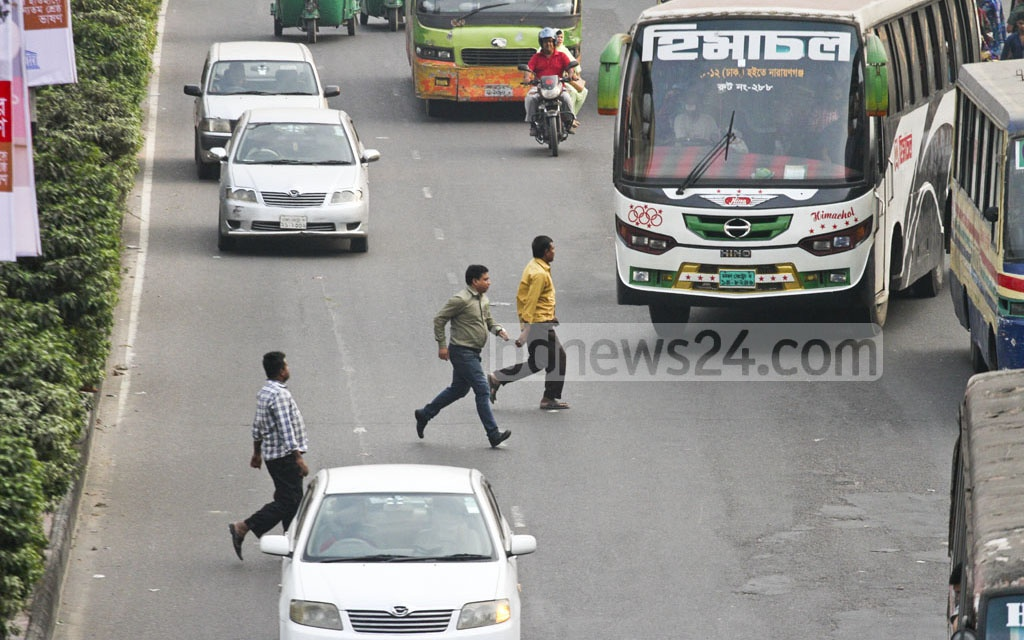 Jaywalkers cross the road with the risk of being hit by speedy vehicles at the Farmgate intersection though there is a footbridge nearby. The photo is taken on Monday. Photo: dipu malakar