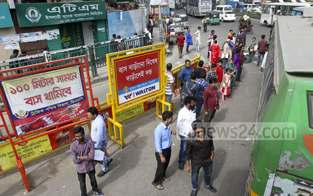 A bus stops to pick up and drop off passengers right next to a 'buses cannot stop here' sign in Dhaka's Kawran Bazar on Tuesday afternoon. Photo: dipu malakar