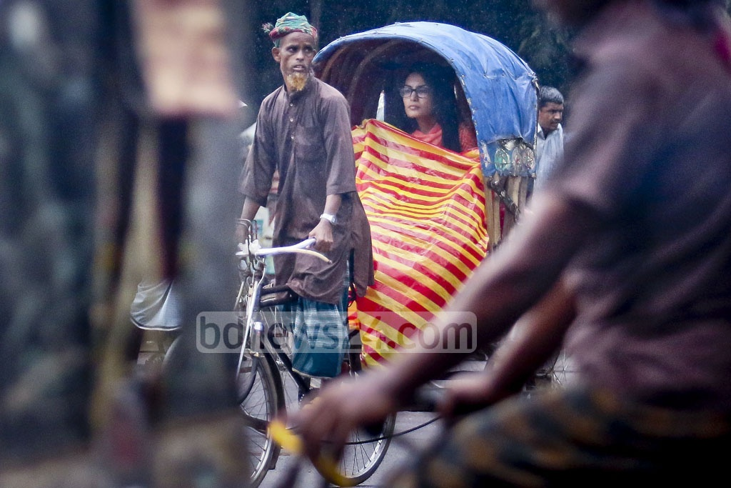 Riders of rickshaw in Dhaka use polythene sheets to cover themselves from drizzle on Thursday in Dhaka University area. Photo: tanvir ahammed